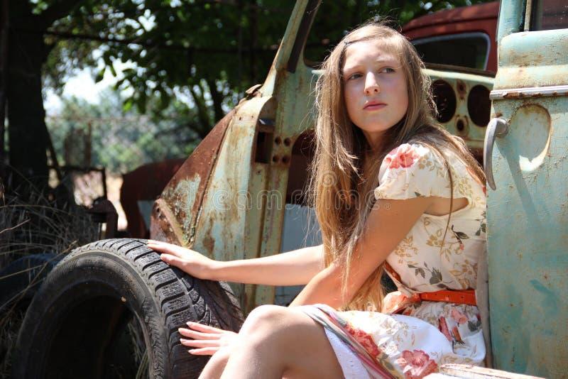 Задумчивая девушка страны от старого сломанного автомобиля стоковое фото