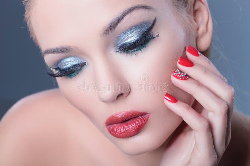 Задумчивая женщина нося славный состав и красные ногти смотря вниз стоковая фотография