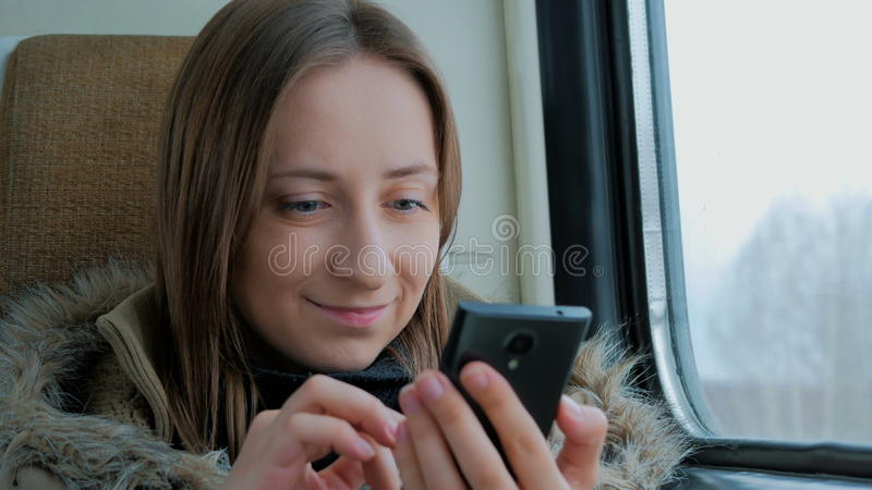 Задумчивая женщина путешествуя на поезде и используя smartphone стоковые фото