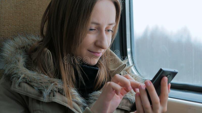 Задумчивая женщина путешествуя на поезде и используя smartphone стоковые изображения rf