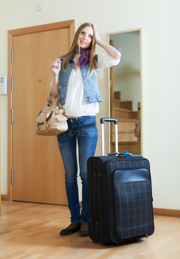 Задумчивая женщина с чемоданом стоковое фото