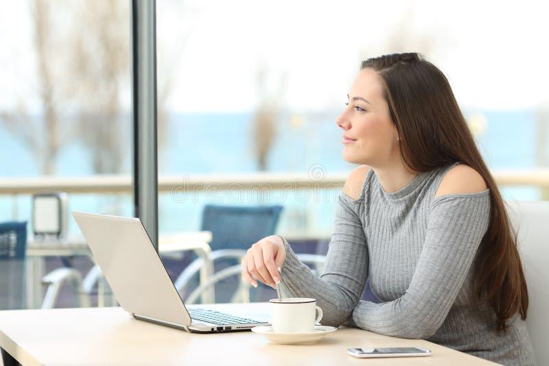 Задумчивая женщина думая в кофейне стоковые фото