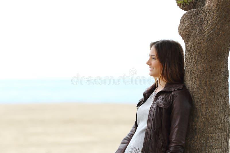 Задумчивая женщина думая на пляже в зиме стоковые изображения