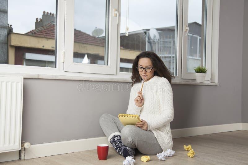 Задумчивая женщина читая что-то дома стоковые фотографии rf