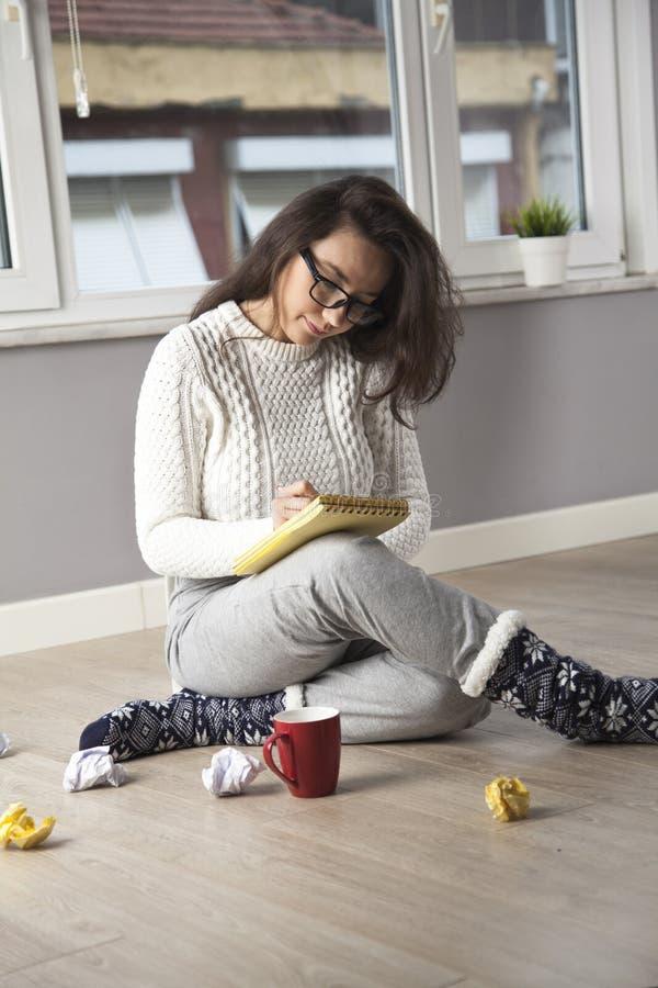 Задумчивая женщина читая что-то дома стоковое изображение