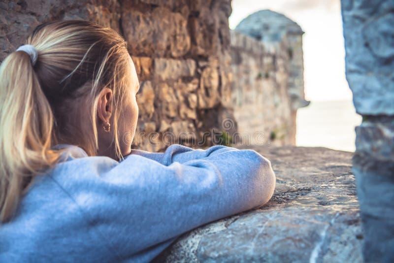 Задумчивая заботливая женщина смотря красивый вид через окно во время захода солнца Солнечный свет освещает сторону женщины Конце стоковая фотография rf