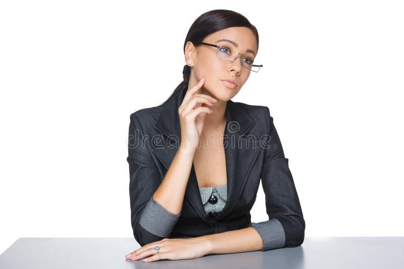 Задумчивая коммерсантка сидя на таблице стоковое изображение rf