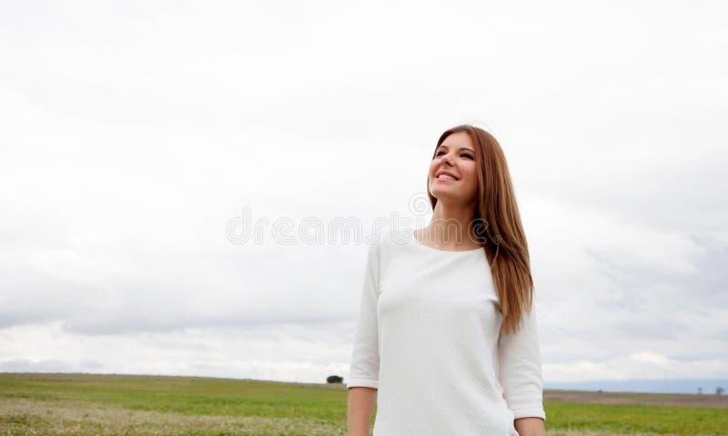 Задумчивая милая женщина ослабленная на луге стоковые фотографии rf
