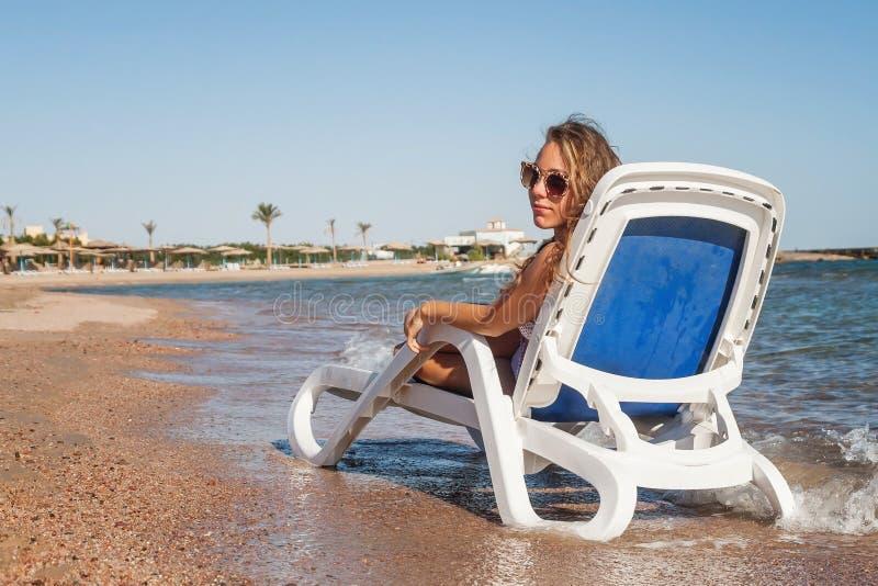 Задумчивая молодая женщина в солнечных очках сидит в deckchair, aga стоковые фото