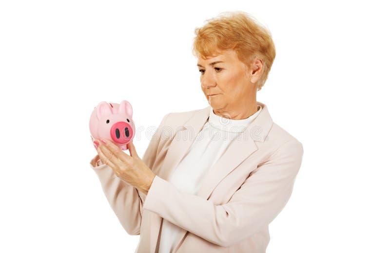 Задумчивая пожилая женщина держа копилку стоковые изображения