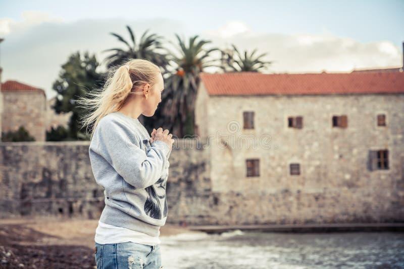 Задумчивая сиротливая женщина стоя на пляже и смотря в волосы женщины ветра расстояния дуя стоковые изображения