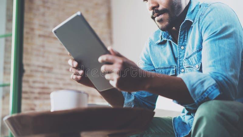 Задумчивый африканский человек используя таблетку для видео- переговора пока ослабляющ на софе в современном офисе Концепция дете стоковое изображение