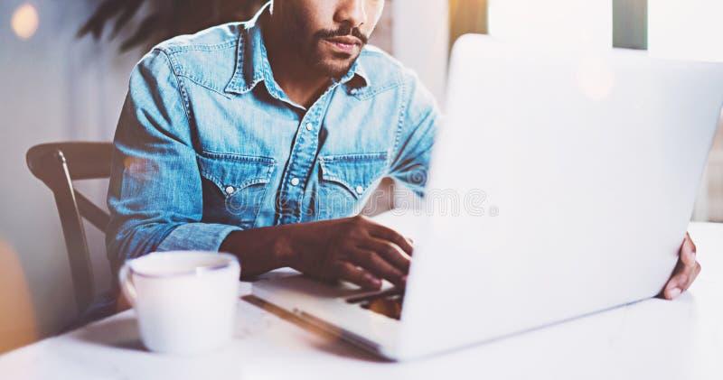 Задумчивый бородатый африканец работая дома пока сидящ деревянный стол Используя современную компьтер-книжку для нового поиска ра стоковые фотографии rf