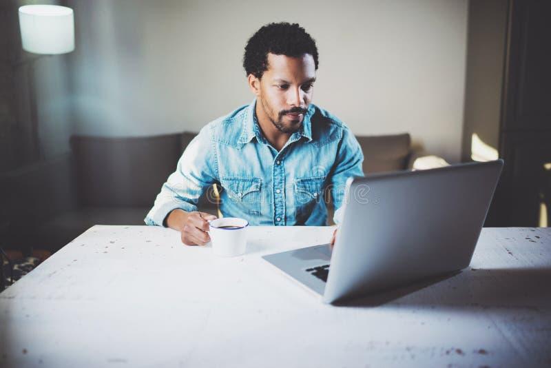 Задумчивый бородатый африканский человек используя компьтер-книжку дома пока кофе выпивая чашки черный на деревянном столе Концеп стоковое изображение rf