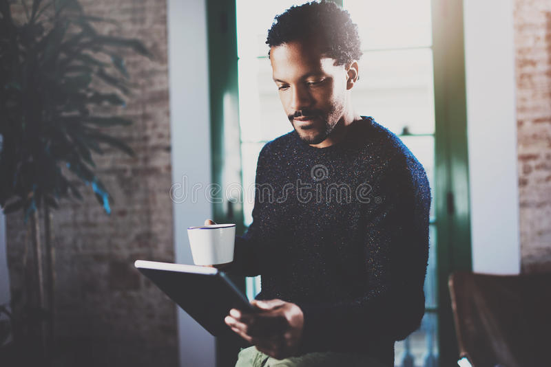 Задумчивый бородатый африканский человек используя таблетку пока держащ белую керамическую чашку в руке на современном coworking  стоковые фото