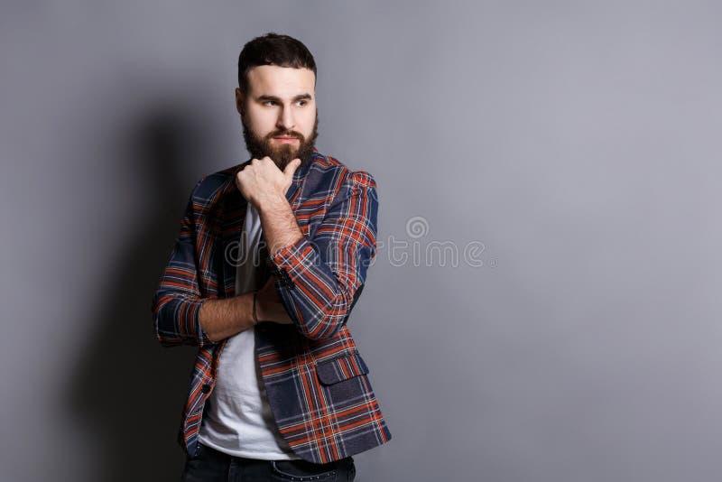 Задумчивый бородатый человек битника с рукой на подбородке стоковые фото