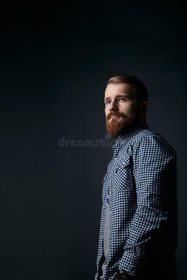 Задумчивый красный бородатый портрет студии человека на темной предпосылке стоковые фото