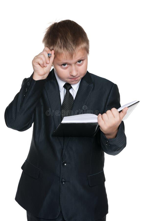 Задумчивый молодой мальчик с тетрадью стоковые фотографии rf