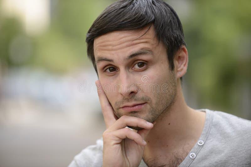 Задумчивый молодой человек outdoors стоковое фото rf