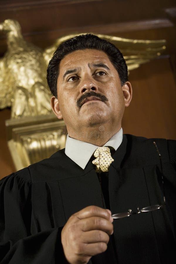 Задумчивый судья держа стекла стоковая фотография