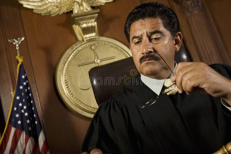 Задумчивый судья сидя в суде стоковые фото