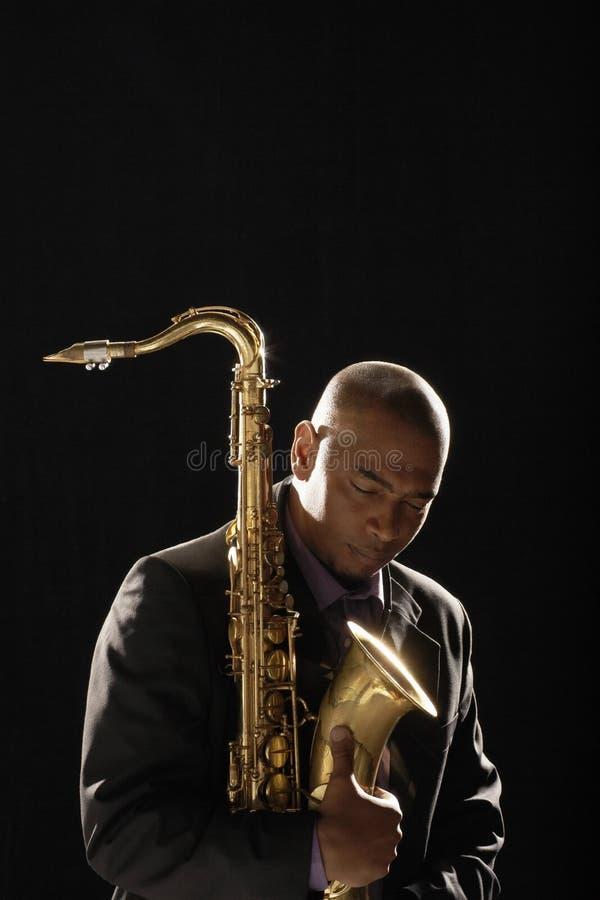 Задумчивый человек при саксофон смотря вниз стоковое фото rf