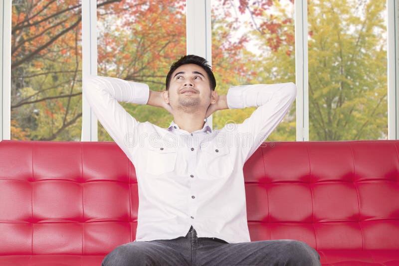 Задумчивый человек сидя на софе пока смотрящ вверх стоковое изображение