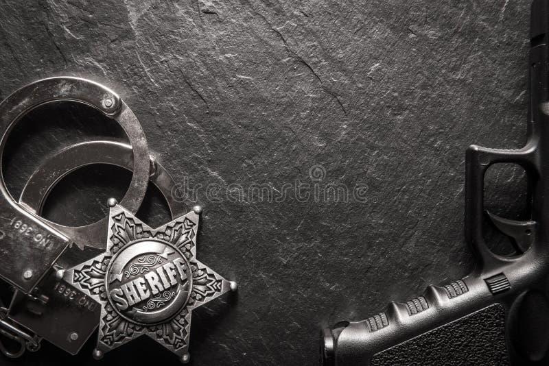 Звезда и наручники шерифа на черной таблице шифера стоковая фотография rf