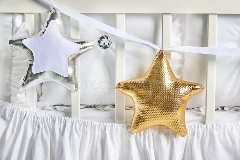 Звезда серебра и золота сформировала подушки на белой кроватке младенца стоковое изображение rf