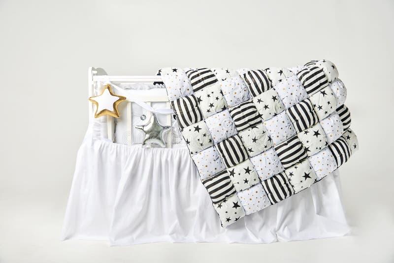 Звезда серебра и золота сформировала подушки и одеяло заплатки на белой кроватке младенца стоковое фото rf