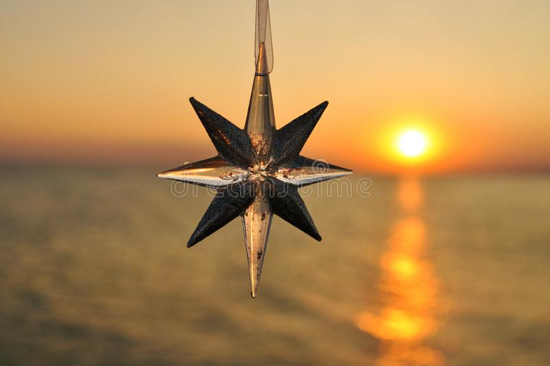 Звезда украшения рождества на предпосылке захода солнца на море горизонтально стоковые изображения rf