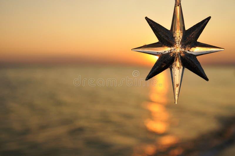 Звезда украшения рождества на предпосылке захода солнца на море стоковое изображение rf