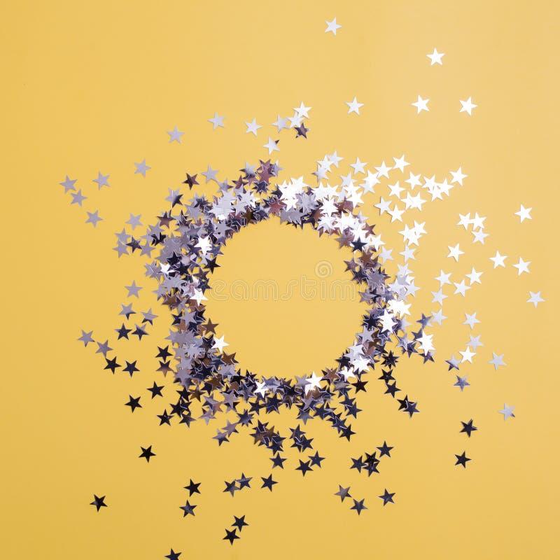Звездообразный confetti разбросал на желтую предпосылку Торжество и партия, концепция r стоковая фотография rf