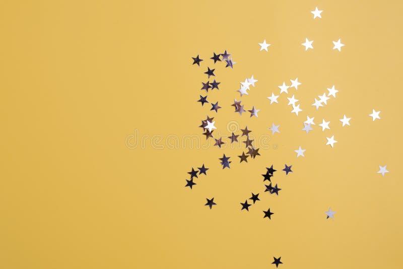 Звездообразный confetti разбросал на желтую предпосылку Торжество и партия, концепция r бесплатная иллюстрация