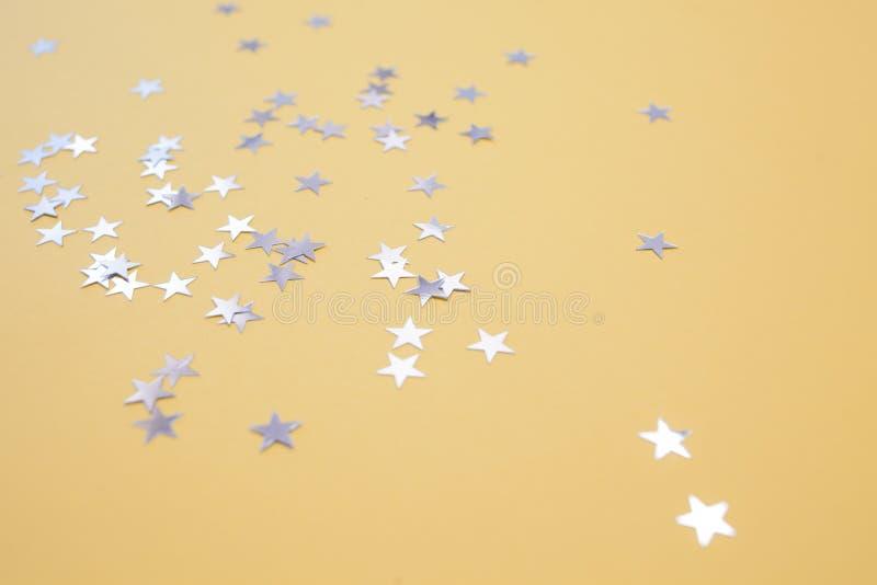 Звездообразный confetti разбросал на желтую предпосылку Торжество и партия, концепция r стоковое фото rf
