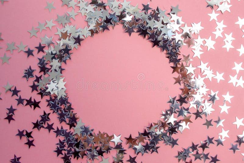 Звездообразный confetti разбросал на розовую предпосылку Торжество и партия, концепция r стоковая фотография