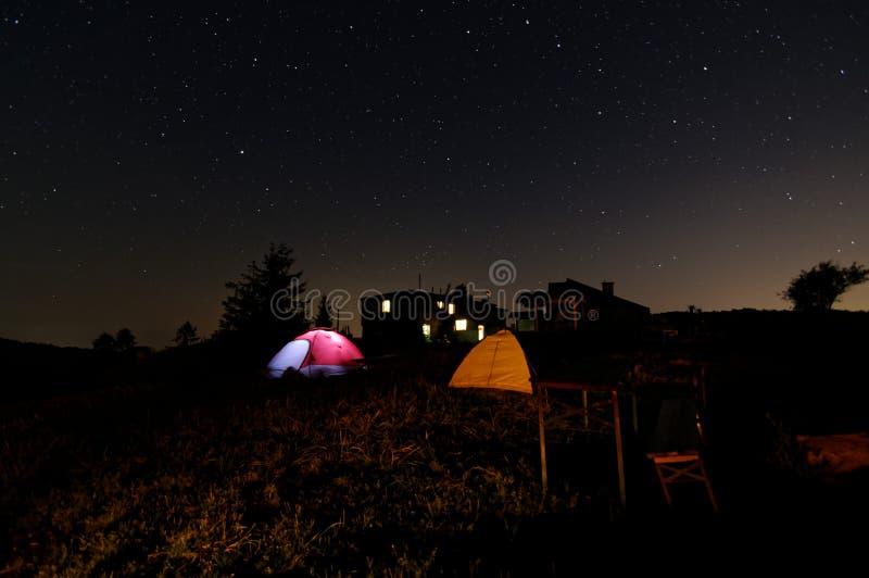 Звездная ночь под шатрами 2 шатра рядом друг с другом Деревянное укрытие в предпосылке стоковые фото