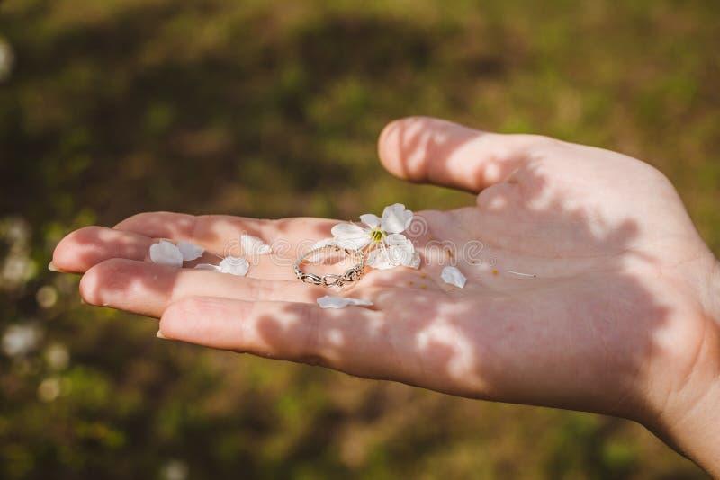 Звените с лепестками цветка на руке ` s женщины Влюбленность настроения стоковая фотография