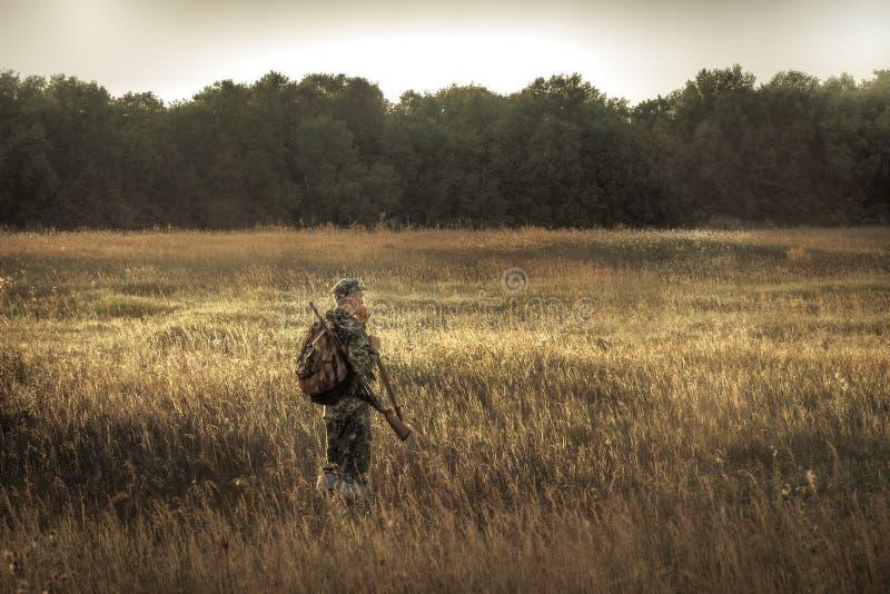 Звероловство охотника в полесье сельского поля близрасположенном на заходе солнца во время сезона звероловства стоковые изображения rf
