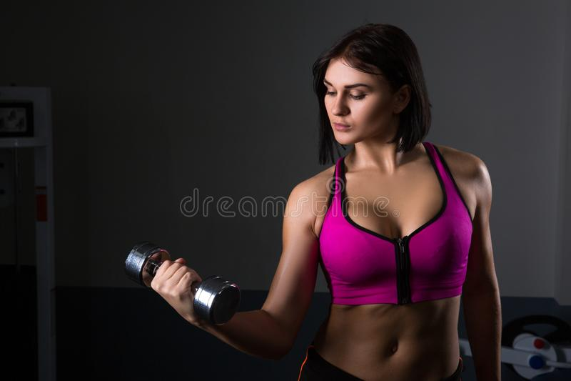 Зверская атлетическая женщина нагнетая вверх muscles с гантелями стоковые изображения rf