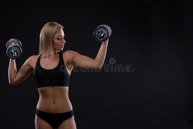 Зверская атлетическая женщина нагнетая вверх muscules с гантелями стоковые фото