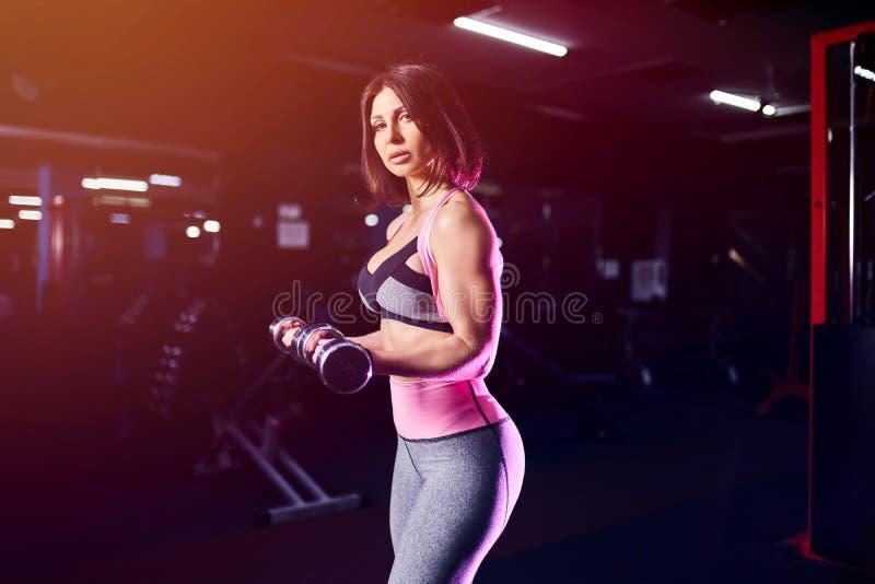 Зверская атлетическая женщина нагнетая вверх muscules с гантелями стоковая фотография