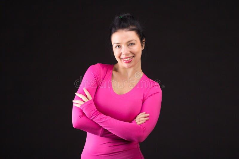 Зверская атлетическая женщина играет шарик на черноте стоковая фотография rf