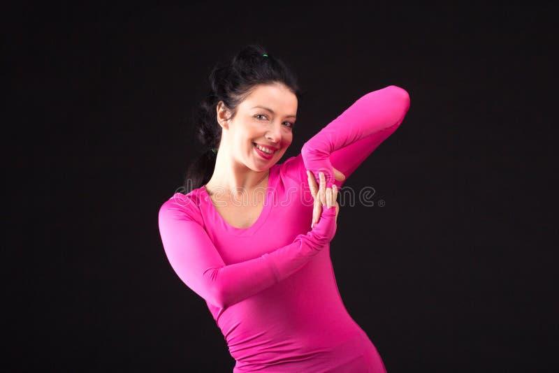 Зверская атлетическая женщина играет шарик на черноте стоковые изображения rf