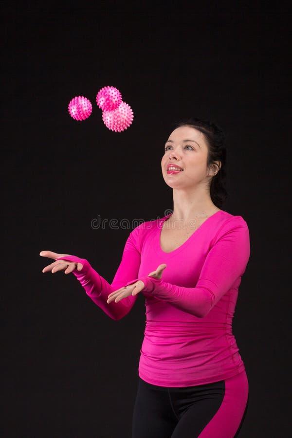 Зверская атлетическая женщина играет шарик на черноте стоковое изображение