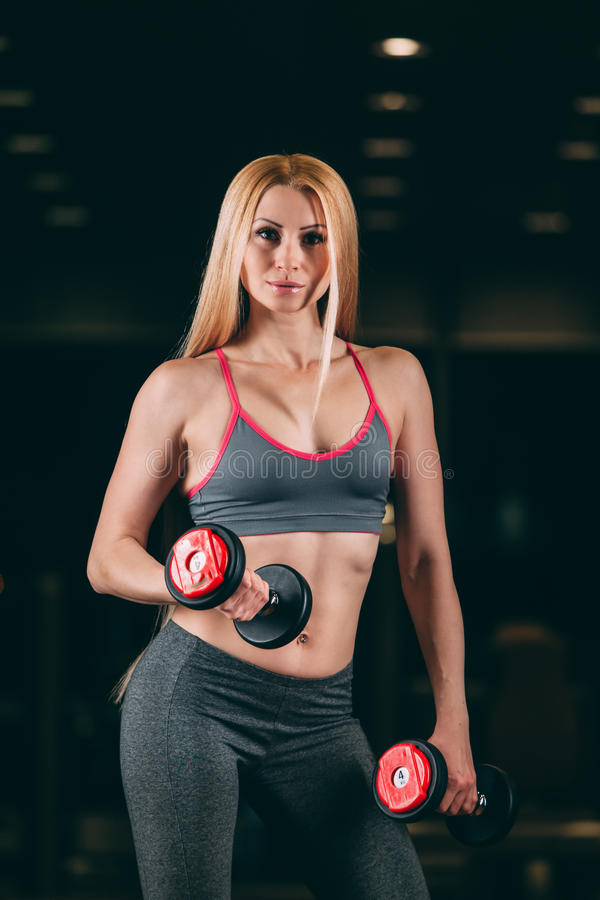 Зверская атлетическая женщина нагнетая вверх muscles с гантелями в спортзале стоковая фотография