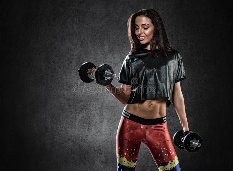 Зверская атлетическая женщина нагнетая вверх muscules с гантелями стоковое фото rf