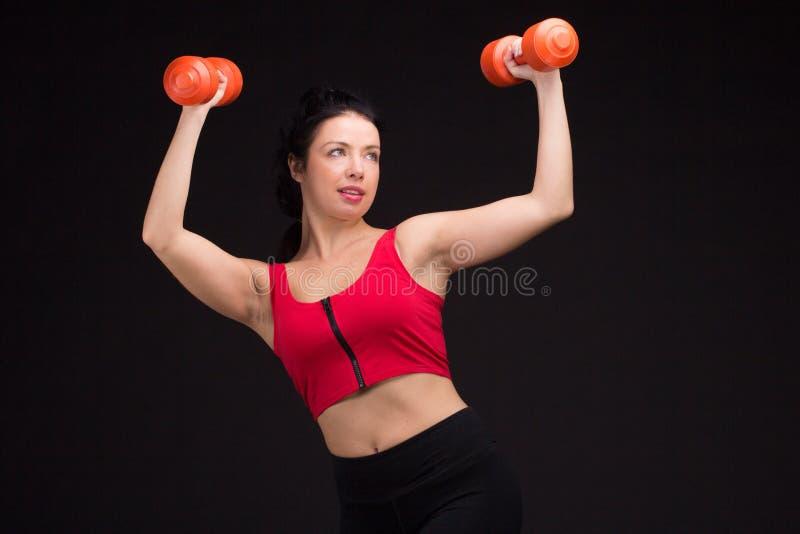 Зверская атлетическая женщина нагнетая вверх muscules с гантелями стоковое фото
