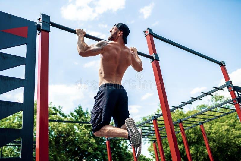 Зверский атлетический человек делая pull-up тренировки на поперечине стоковое фото rf