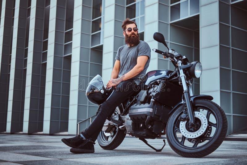 Зверский бородатый мужчина в серой футболке и черных брюках держит шлем сидя на его выполненном на заказ ретро мотоцикле против стоковое изображение rf